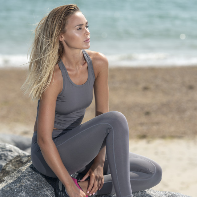 """attractive sporty woman sitting on rocks by the sea resting. sportswoman."" stock image"