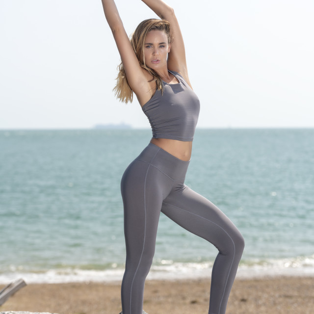 """fit sporty woman stretching her arms, warming up exercises outside by the sea"" stock image"
