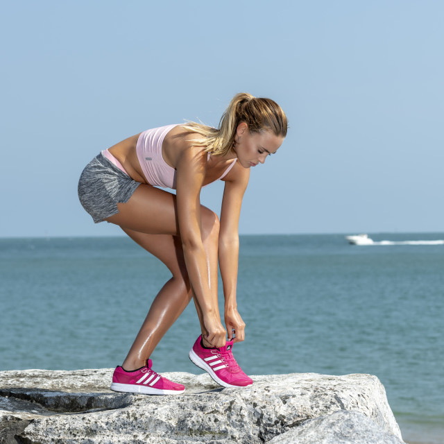"""woman jogger doing up her trainers before running by the sea."" stock image"