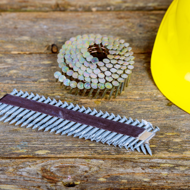 """""""Nails for pneumatic nail gun on wooden background."""" stock image"""