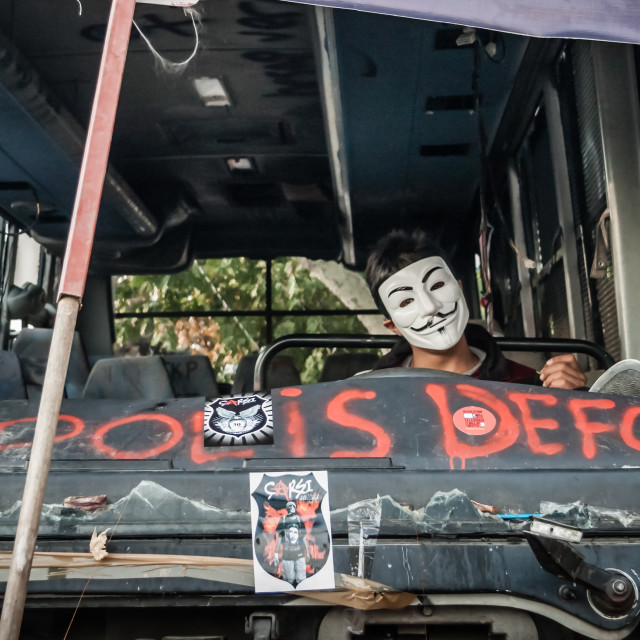 """""""ISTANBUL, TURKEY - JUNE 5, 2013 : Masked Protestor Seats on the Driver Seat of a Destroyed City Bus , after first Protes"""" stock image"""