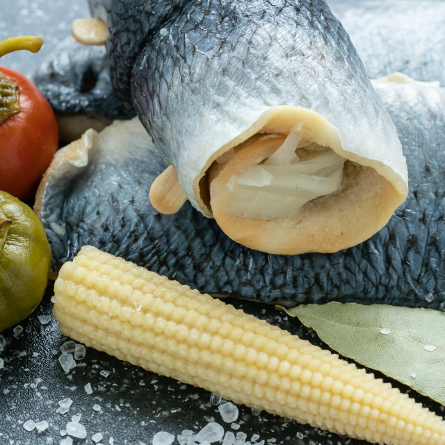 """Saltwater marinated fish, cold appetizer. Herring fillet marinated on black cutting board"" stock image"