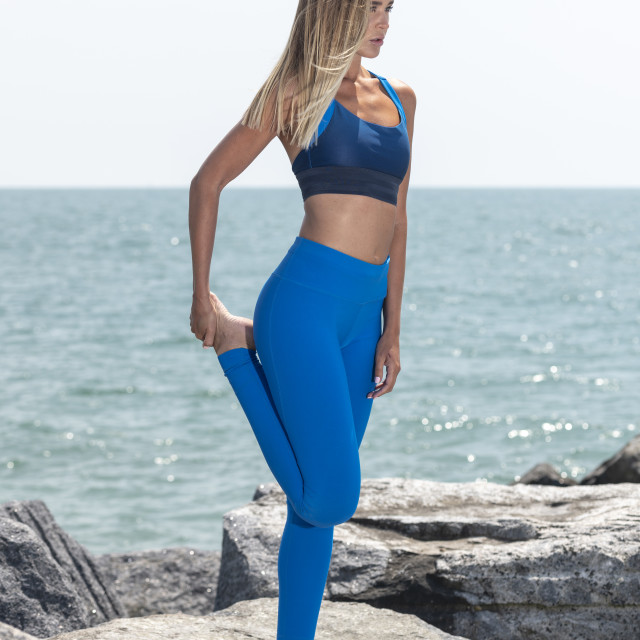 """attractive sporty woman wearing sportswear doing a leg stretch standing on rocks by the ocean"" stock image"