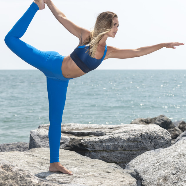 """attractive woman practicing yoga outside standing on rocks by the ocean doing the dancer pose"" stock image"