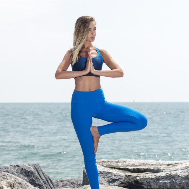 """attractive woman practicing yoga outside standing on rocks by the ocean doing the tree pose"" stock image"