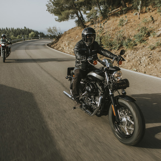 """Man riding a black classic American motorcycle on the road in the mountains."" stock image"