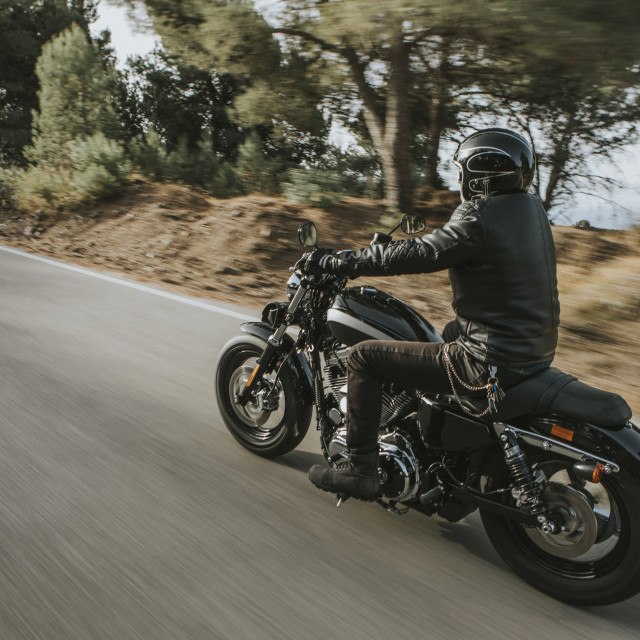 """""""Man in black leather jacket riding a motorcycle on the road across the mountain."""" stock image"""