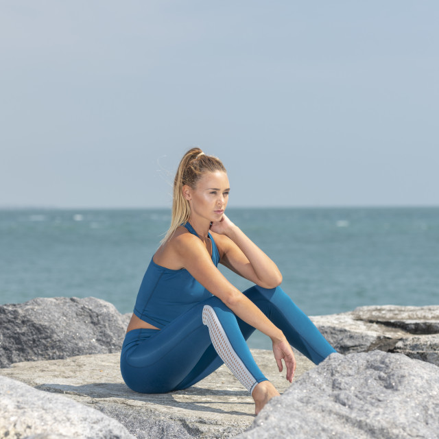 """attractive sporty woman sitting on rocks by the sea resting after exercise"" stock image"