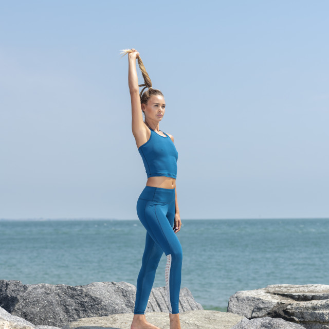 """fit woman wearing sportswear standing on rocks by the sea pulling on her ponytail hair."" stock image"