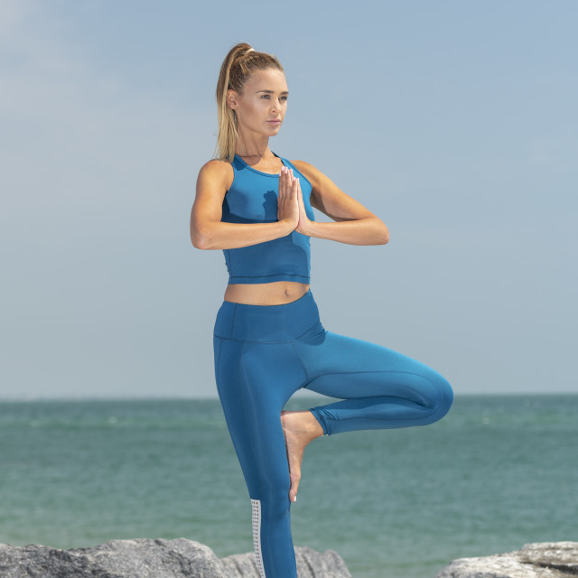 """attractive sporty woman practicing yoga standing on rocks by the sea doing a tree pose"" stock image"