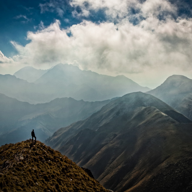 """""""Man on a peak looking at the mountains."""" stock image"""