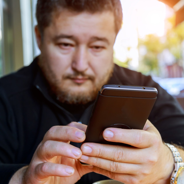 """""""A middle-aged man sits in a coffee shop with a telephone"""" stock image"""