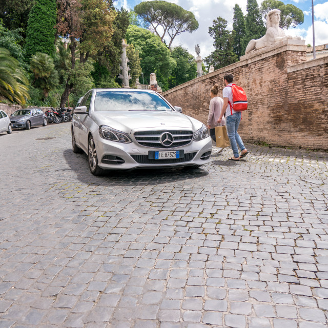 """Car driving down cobblestone street in Rome"" stock image"
