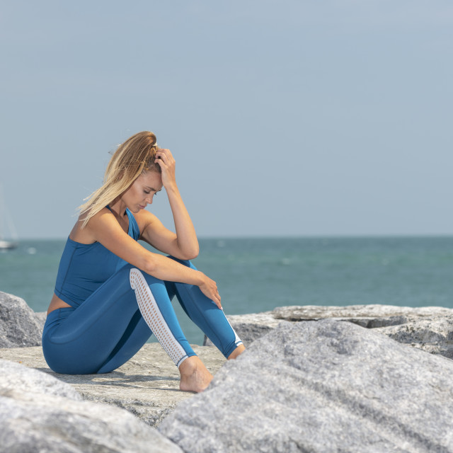 """fit sports woman exhausted after exercise sitting on rocks by the sea with her head in her hands"" stock image"
