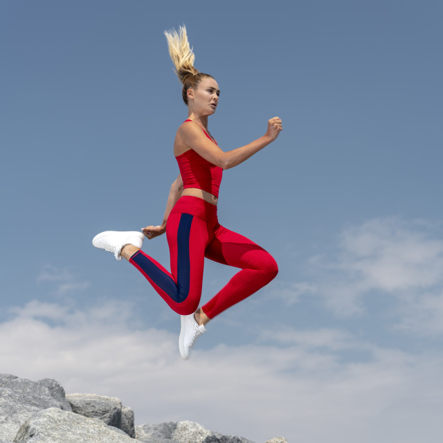 """attractive sporty woman running and jumping across rocks, keeping fit."" stock image"