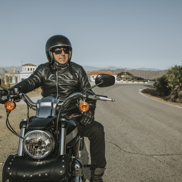 """""""Man with black helmet, jacket and sunglasses standing on a classic American motorcycle"""" stock image"""