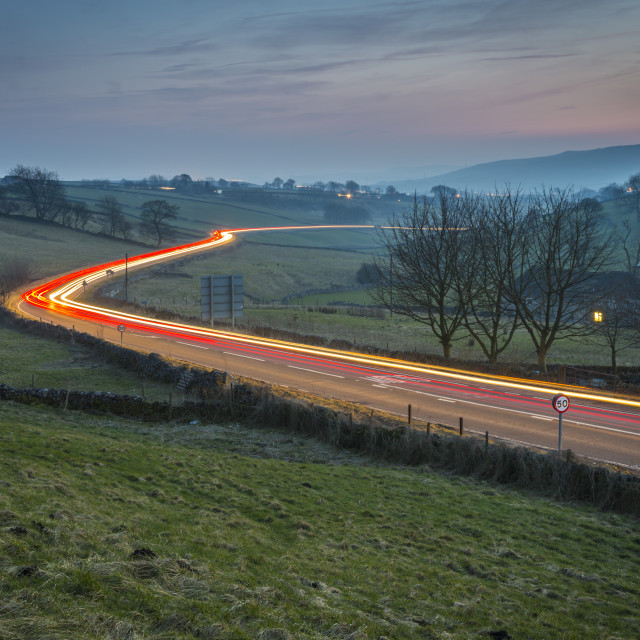 """""""View of vehicle trail lights on A623 at Sparrowpit at dusk, Peak District..."""" stock image"""