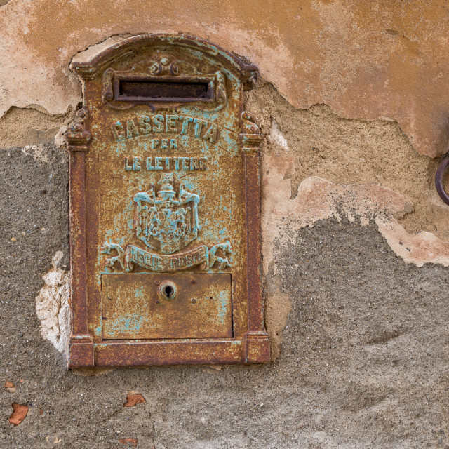 """""""A rusty old mail box and horse tie embedded in a wall."""" stock image"""