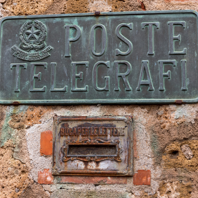 """""""Metal post and telegraph sign and Letter box in the village of Sovano in Tuscany , Italy"""" stock image"""