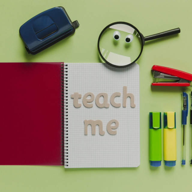 """""""School concept with """"Teach me"""" lettering made with wood, on a notebook."""" stock image"""