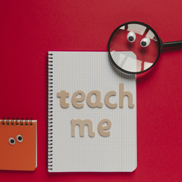 """""""Wooden """"Teach me"""" lettering on a school class and magnifying glass with eyes looking at it."""" stock image"""