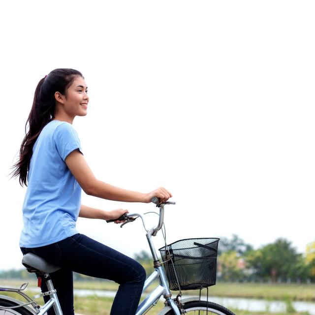 """""""Girl is biking with sky."""" stock image"""
