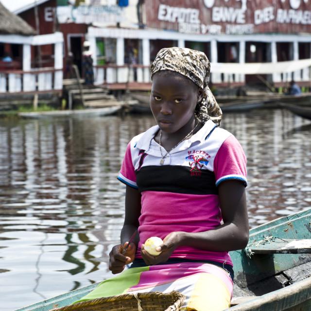 """Girl in canoe with fruit, Ganvie, Benin."" stock image"