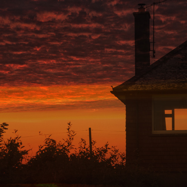 """""""Dramatic red sunset and house"""" stock image"""