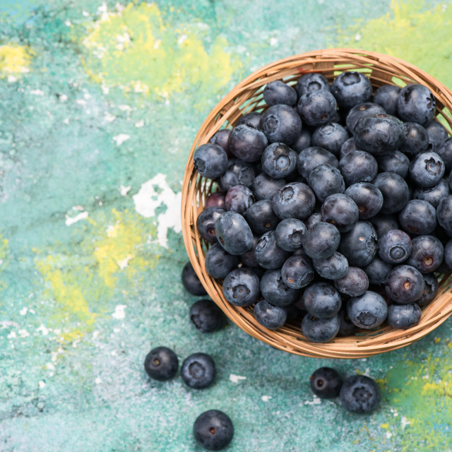 """Fresh ripe blueberry in basket, copy space on wooden board"" stock image"