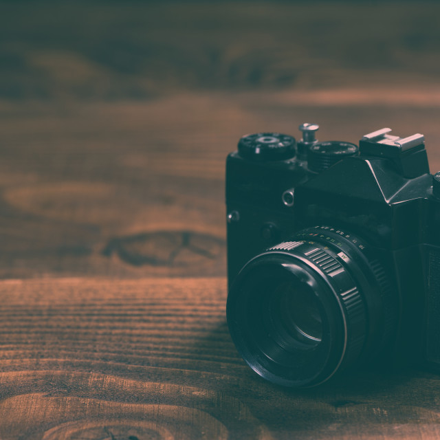 """Vintage film camera on wooden background with copy space"" stock image"