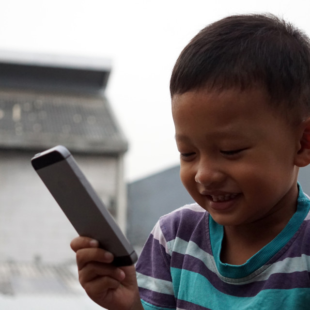 """Child make video call by smartphone on the roof top"" stock image"