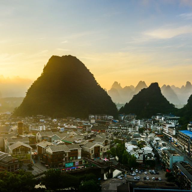 """Sunrise in Yangshuo China over the karst rocks and city"" stock image"