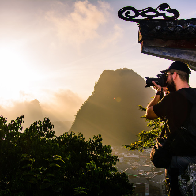 """Photographer capturing sunrise over karst rocks in Yangshuo Chin"" stock image"
