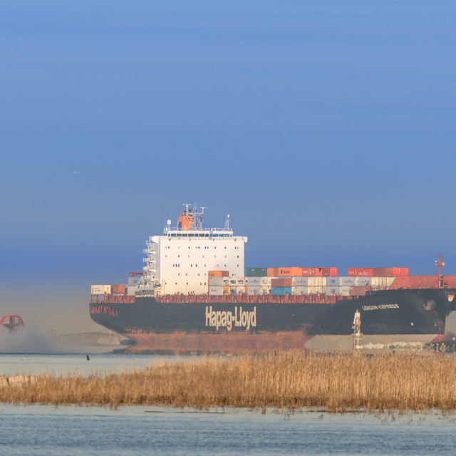 """morning arrival of freighter into the Fraser Delta, a hovercraft passes astern"" stock image"