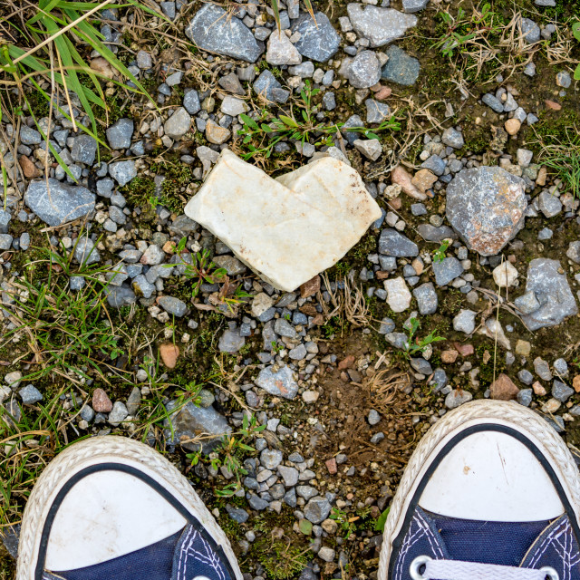 """""""Top view of heart shaped white stone and sneakers"""" stock image"""