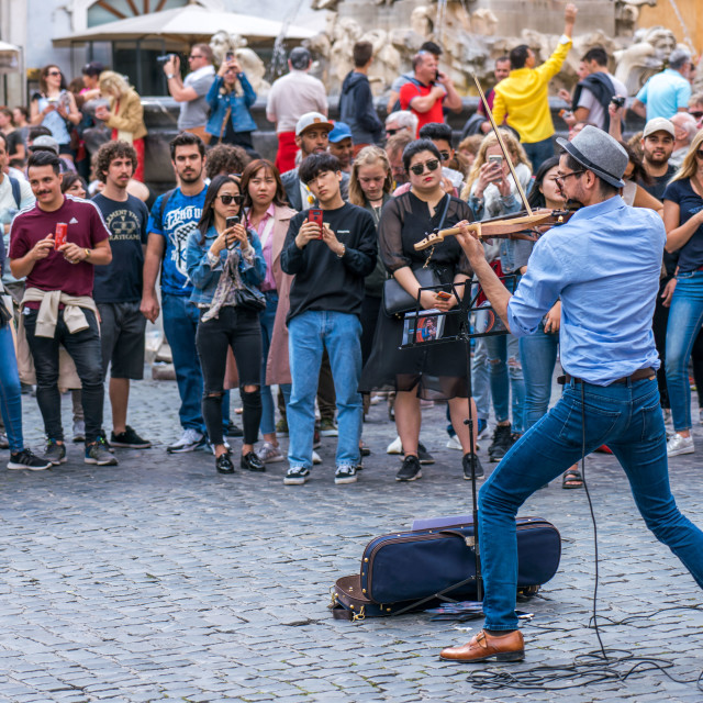 """Street artist and violinist plays for the crowd in front of the"" stock image"