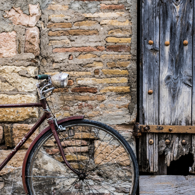 """""""Old bicycle recharged on a rustic wall in a village street of medieval origin in the village of Alquezar in the province of Huesca in Aragon Spain Europe"""" stock image"""