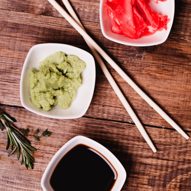 """Sticks, Wasabi, soy sauce and pickled ginger for sushi on brown wooden table background. Top view"" stock image"