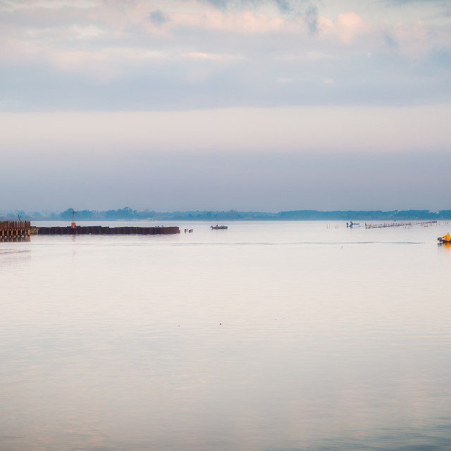 """""""Lesina and its lake. Fisherman in a boat near wooden walkway"""" stock image"""