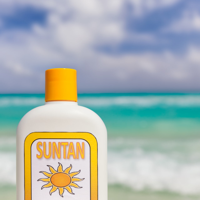 """Suntan lotion with caribbean ocean in background"" stock image"