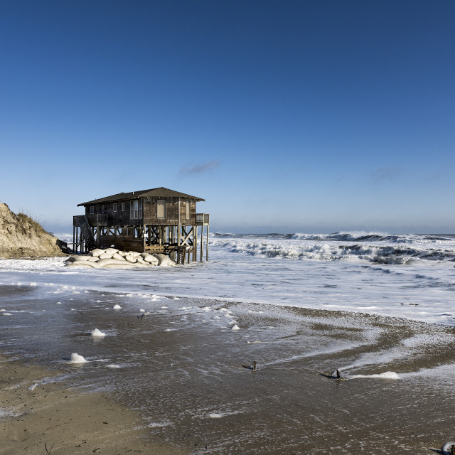 """Beach house on stilts surrounded by high tide surf, Nags Head"" stock image"