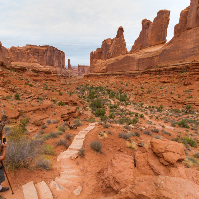 """Tourist taking a picture of Park Avenue in Arches National Park"" stock image"