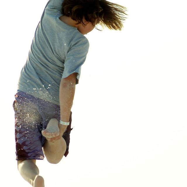 """""""Boy Jumping Over Sand Dunes"""" stock image"""