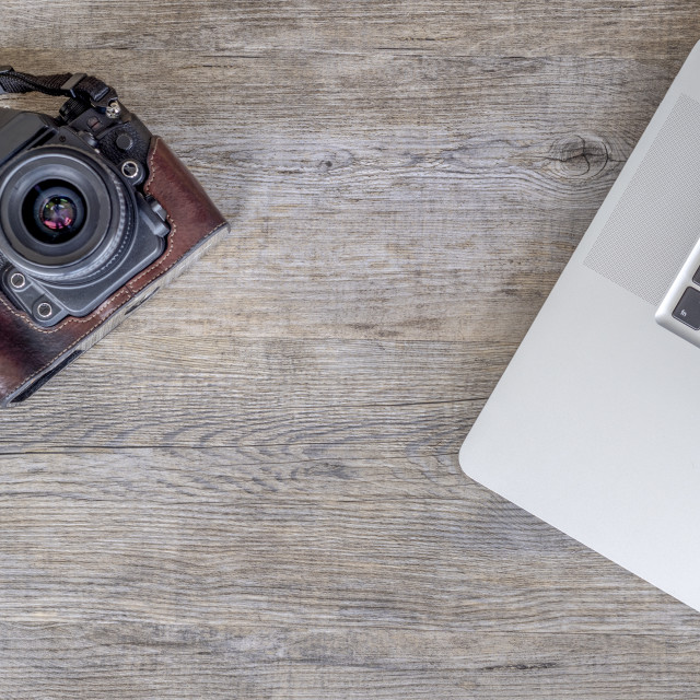 """flat lay, wooden table top with laptop computer and a retro camera"" stock image"