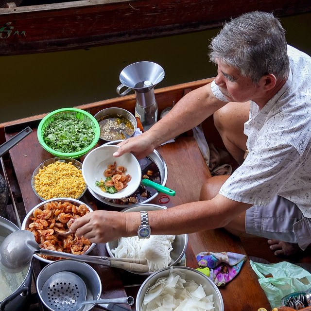 """Man Preparing Food at Damnoen Saduak Floating Market Near Bangkok, Thailand"" stock image"