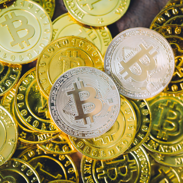 """Many bitcoins laying all over wooden background"" stock image"