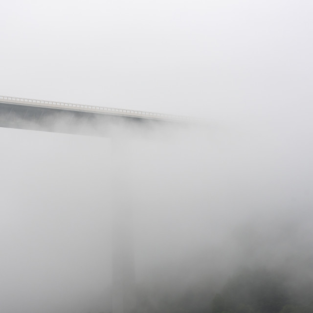 """Silhouette of a tall modern bridge covered by mist"" stock image"