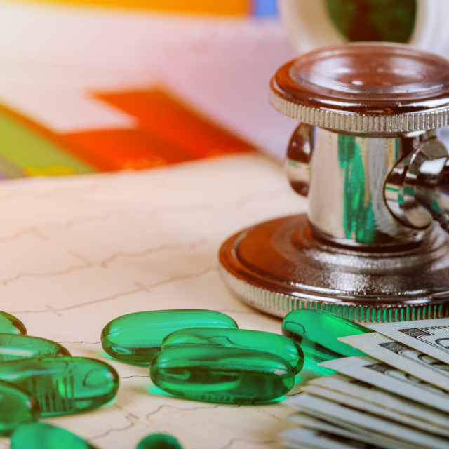 """""""Medical stethoscope head on cardiogram chart with pile of pills and dollars..."""" stock image"""