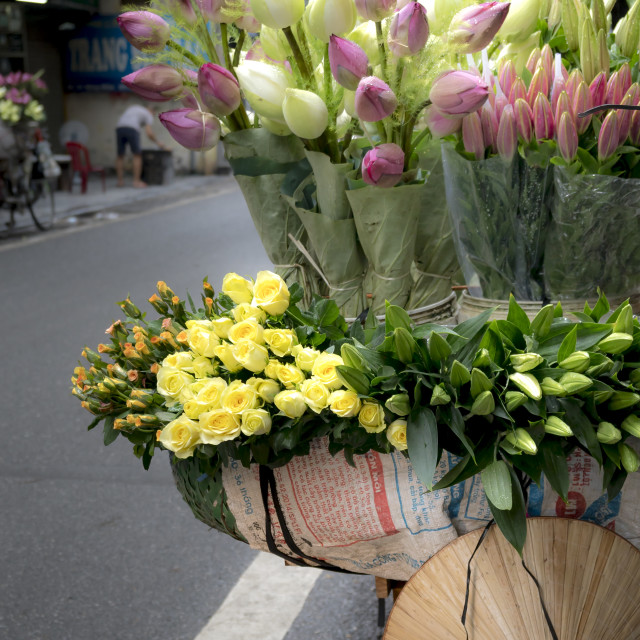 """The street vendors in Hanoi, Vietnam. The Rural woman selling fresh flowers in a busy street."" stock image"