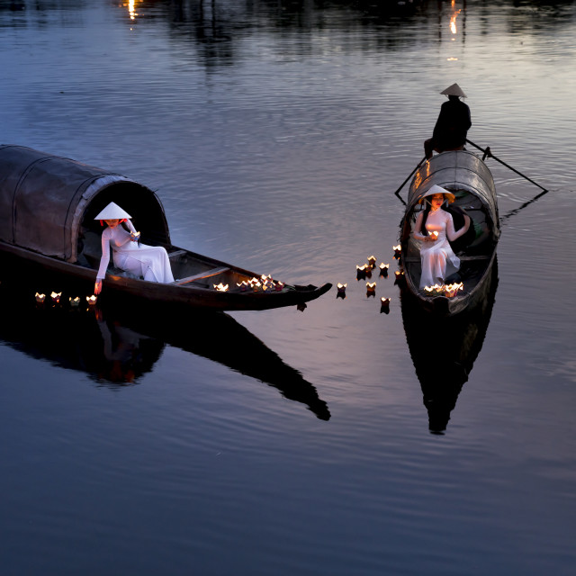 """""""Vietnamese girls with white tradition Ao Dai are lighting the candle in the lantern to pray in the river."""" stock image"""